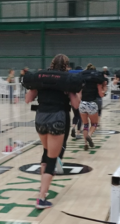 crossfit chicks working out during crossfit competition with sandbags