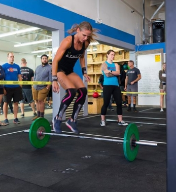 crossfit girls doing burpees over barbell at crossfit competition